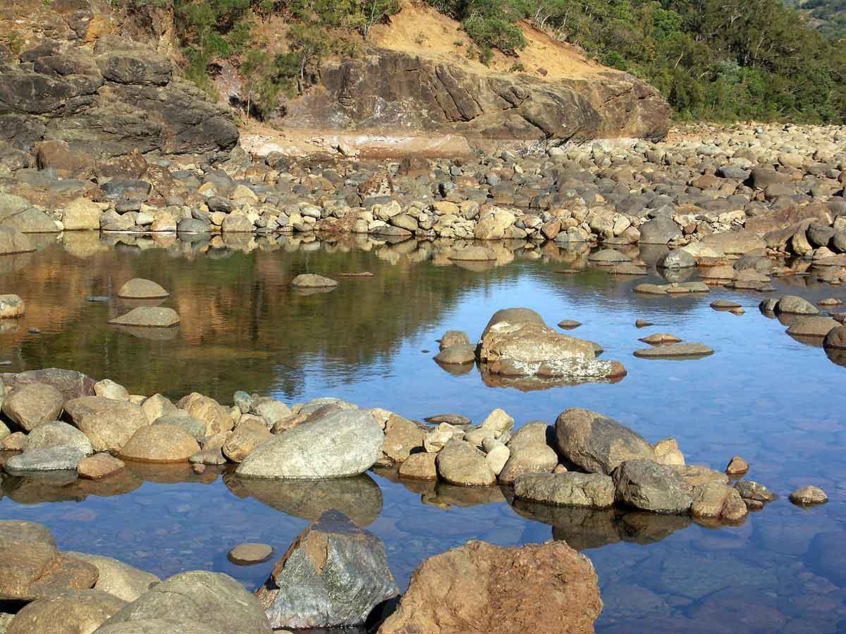 Sur les rives de la Dumbea, bordées de roche de nickel, je vois devant moi une grande sculpture se dressant au milieu de la rivière.